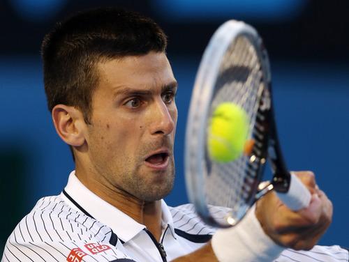 Serbia's Novak Djokovic hits a return to Tomas Berdych of the Czech Republic during their quarterfinal match at the Australian Open tennis championship in Melbourne, Australia, Tuesday, Jan. 22, 2013.  (AP Photo/Dita Alangkara)
