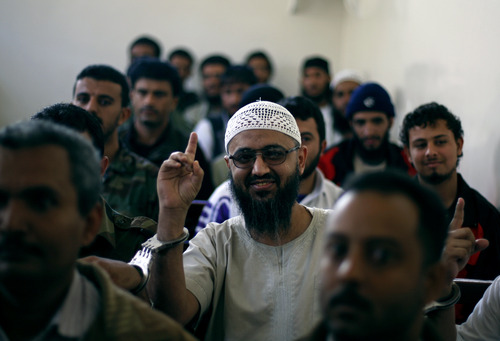 A suspected al-Qaida militant, center, gestures as he attends his trial in a state security court in Sanaa, Yemen, Tuesday, Jan. 22, 2013. U.N. agencies and other aid organizations appealed Tuesday for $716 million in donations to help Yemen which is wracked by militant attacks and instability deal with a deepening humanitarian crisis that includes widespread malnutrition in the Arabian peninsula's poorest country. (AP Photo/Hani Mohammed)