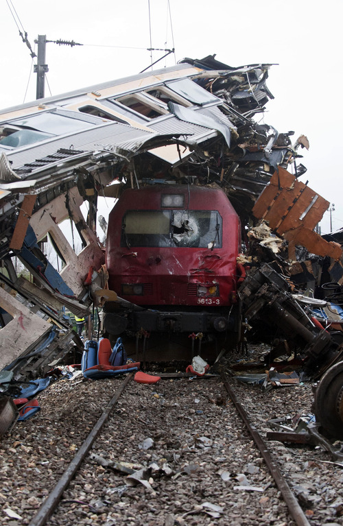 A train sits beneath the carriage of another train after a train crash at a station in Alfarelos, Portugal Tuesday Jan. 22, 2013. Emergency services say a high-speed intercity train rear-ended a local train waiting to enter a station in central Portugal, derailing several carriages leaving a pile of wreckage on Portugal's main north-south line, slightly injuring 21 people. Officials said the local train was waiting to pull into a station near Coimbra, 200 kilometers (120 miles) north of the capital, Lisbon, when the northbound intercity train slammed into it from behind at 9.15 p. m. (2100 GMT) on Monday. (AP Photo/Miguel Teixeira)