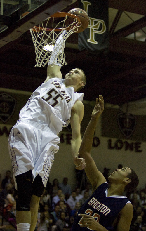 Kim Raff  |  The Salt Lake Tribune (left) Lone Peak player Eric Mika dunks the ball over the head of Brighton player Tremaine Nisson for a loose ball during a game at Lone Peak High School in Highland on November 28, 2012. Lone Peak went on to win the game.