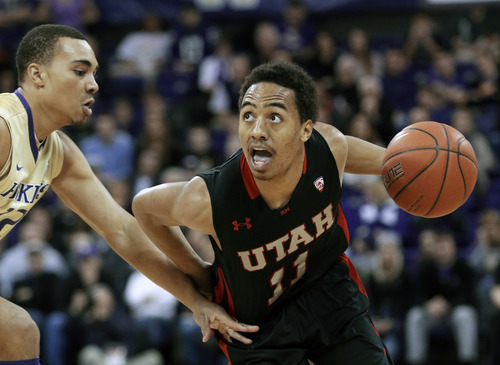 Utah's Brandon Taylor (11) eyes the basket as drives against Washington's Andrew Andrews in the first half of an NCAA college basketball game Saturday, Jan. 19, 2013, in Seattle. (AP Photo/Elaine Thompson)