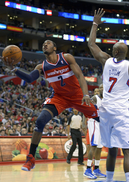 Washington Wizards guard John Wall, left, puts up a shot as Los Angeles Clippers forward Lamar Odom defends during the second half of their NBA basketball game, Saturday, Jan. 19, 2013, in Los Angeles. The Clippers won 94-87. (AP Photo/Mark J. Terrill)