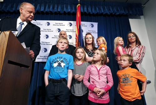 Arizona Attorney General Tom Horne, left, looks at Ruby Jessop, rear center, and her six children during a news conference, Tuesday, Jan. 22, 2013, in Phoenix.  Horne discussed how his agency and others, including Ruby's sister Flora Jessop, top right, and a Mohave County Supervisor, Buster Johnson, rear left, helped Ruby and her six children leave a polygamist sect along the Utah-Arizona border.(AP Photo/Ross D. Franklin)