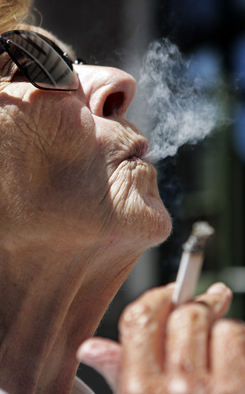 FILE - In a June 11, 2007 file photo, Helen Heinlo smokes outside of a coffee shop in Belmont, Calif. Millions of smokers could be priced out of health insurance because of tobacco penalties in President Barack Obama's health care law, say experts. The Affordable Care Act allows health insurers to charge smokers buying an individual policy up to 50 percent higher premiums starting next Jan. 1. For a 55-year-old smoker, the penalty could reach nearly $4,250 a year. A 60-year-old could wind up paying nearly $5,100 on top of premiums. (AP Photo/Paul Sakuma, File)