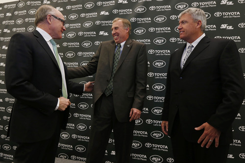 John Idzik, center, reacts while standing next to New York Jets owner Woody Johnson, left, and head coach Rex Ryan during an NFL football news conference introducing Idzik as the team's new general manager, Thursday, Jan. 24, 2013, in Florham Park , N.J. (AP Photo/Julio Cortez)