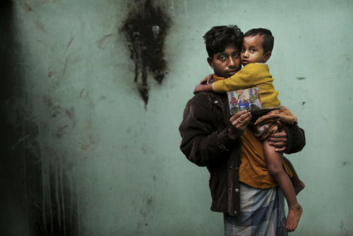 In this Friday, Dec. 21, 2012 photo, Bangladeshi Abdul Jabbar, 26, holds his son Masum, 18 months, as he displays a photograph of his wife, Mahfouza Kahtun, 22, a sewing machine operator who died in the fire at Tazreen Fashions, in the garment district in Ashulia, near Dhaka, Bangladesh. When fire ravaged the Bangladeshi garment factory, killing 112 workers, dozens of their families did not even have a body to bury because their loved ones' remains were burned beyond recognition. Two months later, they have yet to receive any of the compensation they were promised - not even their relatives' last paychecks.  (AP Photo/Kevin Frayer)