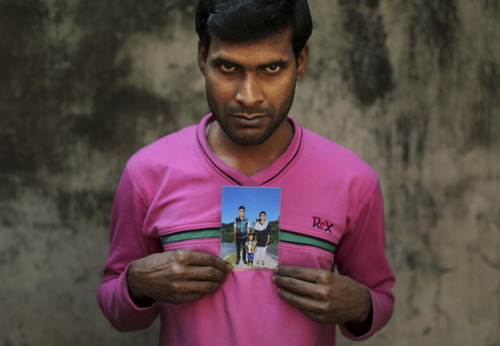 In this Friday, Dec. 21, 2012 photo, Bangladeshi Mohammed Habibur displays a photograph of his wife, Rashida Akhtar, a sewing machine operator who died in the fire at Tazreen Fashions, in the garment district in Ashulia, near Dhaka, Bangladesh. When fire ravaged the Bangladeshi garment factory, killing 112 workers, dozens of their families did not even have a body to bury because their loved ones' remains were burned beyond recognition. Two months later, they have yet to receive any of the compensation they were promised - not even their relatives' last paychecks. (AP Photo/Kevin Frayer)