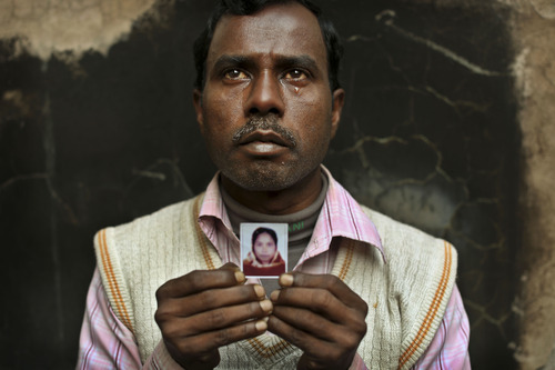 In this Friday, Dec. 21, 2012 photo, Bangladeshi Mohammed Hannan, 35, weeps as he holds a picture of his wife Ahenur, 30, an assistant sewing machine operator who died in the fire at Tazreen Fashions, in the garment district in Ashulia, near Dhaka, Bangladesh. When fire ravaged the Bangladeshi garment factory, killing 112 workers, dozens of their families did not even have a body to bury because their loved ones' remains were burned beyond recognition. Two months later, they have yet to receive any of the compensation they were promised - not even their relatives' last paychecks. The remainder were burnt beyond recognition and their remains are undergoing DNA testing to prevent people from filing fake claims. (AP Photo/Kevin Frayer)