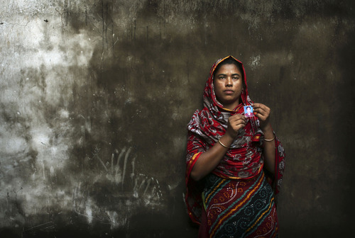 In this Friday, Dec. 21, 2012 photo, Bangladeshi Rumana Begum, 33, holds a photograph of her 18-year-old daughter, Mukhtar Begum, a senior sewing machine operator who died in the fire at Tazreen Fashions, in the garment district in Ashulia, near Dhaka, Bangladesh. When fire ravaged the Bangladeshi garment factory, killing 112 workers, dozens of their families did not even have a body to bury because their loved ones' remains were burned beyond recognition. Two months later, they have yet to receive any of the compensation they were promised - not even their relatives' last paychecks.  (AP Photo/Kevin Frayer)