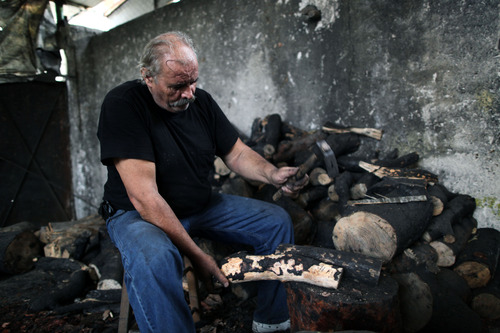 In this picture taken Oct. 15 2012, Grigoris Athanassakis chips bark off logs at his firewood yard in the Athens district of Tavros. A steep increase in heating costs has forced many in crisis-hit Greece to switch from heating oil to wood-burning for warmth. But there's a catch. Illegal loggers are slashing through forests devastated by years of summer wildfires, air pollution from wood smoke is choking the country's main cities and there has been an increase in blazes caused by carelessly attended woodstoves.(AP Photo/Petros Giannakouris)