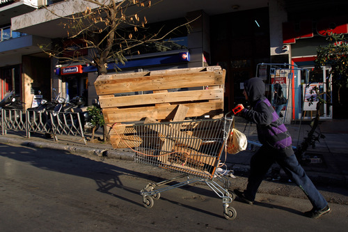 FILE - In this  Jan. 3, 2013, file photo, a youth carts away wooden palettes scavenged from recycling bins to be used as fire wood in the northern city of Thessaloniki, Greece. A steep increase in heating costs has forced many in crisis-hit Greece to switch from heating oil to wood-burning for warmth. But there's a catch. Illegal loggers are slashing through forests devastated by years of summer wildfires, air pollution from wood smoke is choking the country's main cities and there has been an increase in blazes caused by carelessly attended woodstoves.(AP Photo/Nikolas Giakoumidis, File)