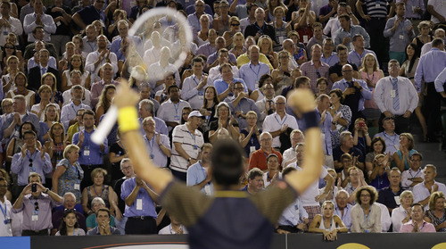 The crowd applauds as Serbia's Novak Djokovic celebrates after defeating Spain's David Ferrer in their semifinal match at the Australian Open tennis championship in Melbourne, Australia, Thursday, Jan. 24, 2013. (AP Photo/Andy Wong)