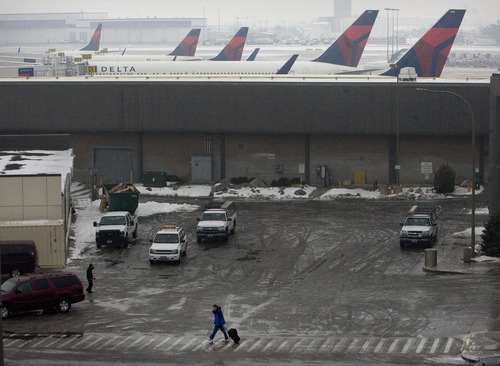 Scott Sommerdorf   |  The Salt Lake Tribune A lone traveler moves between terminals as airplanes were grounded at the Salt Lake City International Airport, Thursday, January 24, 2013.