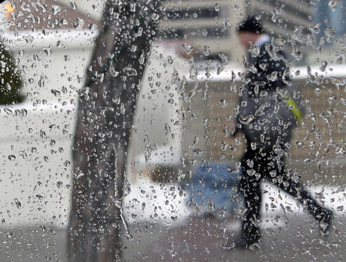Al Hartmann  |  The Salt Lake Tribune A person walks past a car window coated with frozen rain along West Temple Street in Salt Lake City Thursday January 23. Freezing rain is an unusual occurrence in Utah.