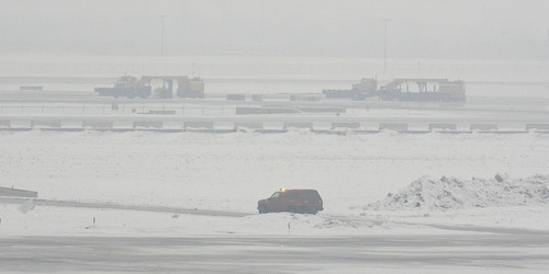 Scott Sommerdorf   |  The Salt Lake Tribune A succession of snowplows and maintenance vehicles worked to clear runways as airplanes were grounded at the Salt Lake City International Airport, Thursday, January 24, 2013.