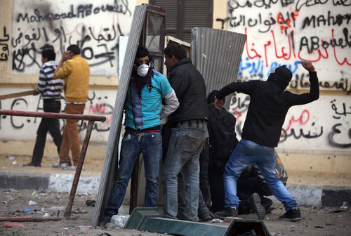 Egyptian protesters take cover as they clash with riot police, not seen, near Tahrir Square, Cairo, Egypt, Friday, Jan. 25, 2013. Two years after Egypt's revolution began, the country's schism was on display Friday as the mainly liberal and secular opposition held rallies saying the goals of the pro-democracy uprising have not been met and denouncing Islamist President Mohammed Morsi. With the anniversary, Egypt is definitively in the new phase of its upheaval. (AP Photo/Khalil Hamra)