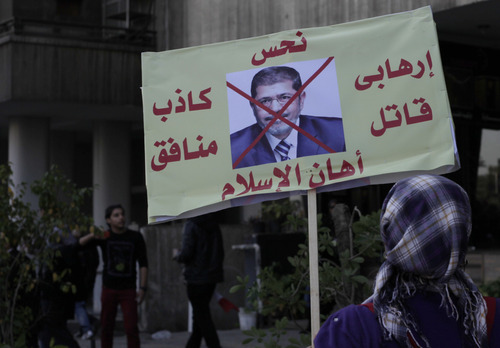 """A woman carries a sign with a photo of Egyptian President Mohammed Morsi and Arabic that reads, """"jinx, terrorist killer, embarrassment to Islam. hypocritical liar,"""" during a march near Tahrir Square, Cairo, Egypt, Friday, Jan. 25, 2013. Egyptian opposition protesters are gathering in Cairo's Tahrir Square to mark the second anniversary of the uprising that toppled Hosni Mubarak's autocratic regime. (AP Photo/Nariman El-Mofty)"""