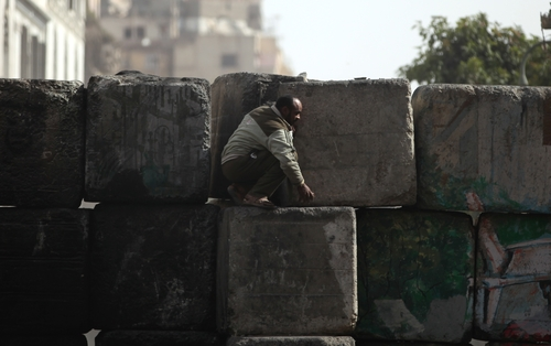 An Egyptian man takes cover during clashes with security forces near Tahrir Square, Cairo, Egypt, Friday, Jan. 25, 2013. Youth activists and opposition groups have called for large rallies to mark the second anniversary of Egypt's Jan. 25, 2011 uprising that toppled long-time authoritarian leader President Hosni Mubarak. (AP Photo/Khalil Hamra)