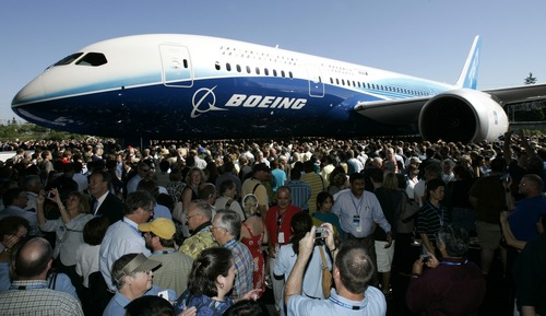 FILE - In this July 8, 2007, file photo, visitors  look at and take photos of the first production model of the new Boeing 787 airplane after it was unveiled to an audience of several thousand at Boeing's assembly plant in Everett, Wash. The Boeing 787 was a plane that promised to be lighter and more technologically advanced than any other, but once production started, the gap between vision and reality quickly widened. The jet that was eventually dubbed the Dreamliner became plagued with manufacturing delays, cost overruns and sinking worker morale. (AP Photo/Ted S. Warren, File)