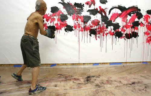 """Rick Egan    The Salt Lake Tribune   81-year-old old Japanese artist, Ushio Shinohara, punches his art on to the canvas, with boxing gloves covered in sponges, at the Central Utah Art Center, Monday, January 21, 2013. Shinohara, is featured in the Sundance documentary film """"Cutie and the Boxer."""""""