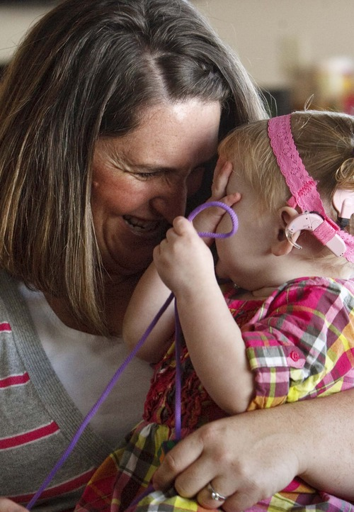 Leah Hogsten  |  The Salt Lake Tribune Sara Doutre plays with daughter Daisy, 22 months, at their home in Willard. Daisy became deaf after contracting a virus called cytomegalovirus in utero. Daisy now wears cochlear implants.