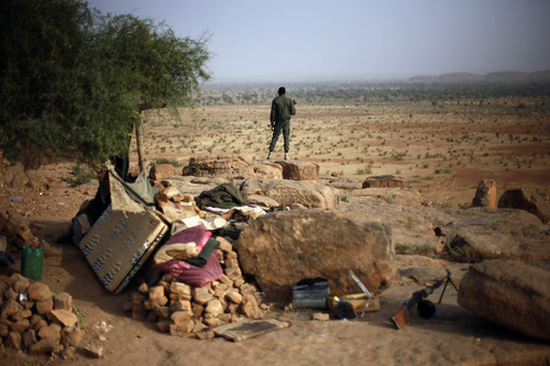 A Malian soldier stands at an observation post outside Sevare, some 620 kms (400 miles)  north of Mali's capital  Bamako Thursday, Jan. 24, 2013.  One wing of Mali's Ansar Dine rebel group has split off to create its own movement, saying that they want to negotiate a solution to the crisis in Mali, in a declaration that indicates at least some of the members of the al-Qaida-linked group are searching for a way out of the extremist movement in the wake of French airstrikes. (AP Photo/Jerome Delay)