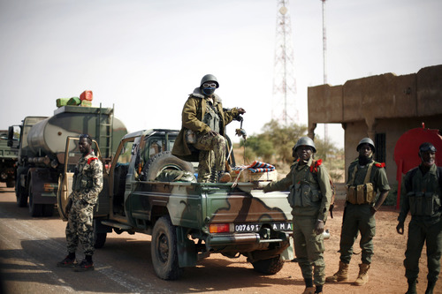 In this image taken during an official visit organized by the Malian army to the town of Konna, some 680 kilometers (430 miles) north of Mali's capital Bamako, Saturday, Jan. 26, 2013, Malian soldiers stand on the back of a pickup truck. One wing of Mali's Ansar Dine rebel group has split off to create its own movement, saying that they want to negotiate a solution to the crisis in Mali, in a declaration that indicates at least some of the members of the al-Qaida linked group are searching for a way out of the extremist movement in the wake of French air strikes. (AP Photo/Jerome Delay)