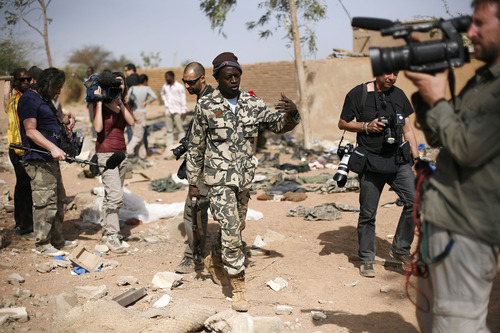 In this image taken during an official visit organized by the Malian army to the town of Konna, some 680 kilometers (430 miles) north of Mali's capital Bamako, Saturday, Jan. 26, 2013, a Malian soldier gestures at journalists to leave the area of a French air strike. One wing of Mali's Ansar Dine rebel group has split off to create its own movement, saying that they want to negotiate a solution to the crisis in Mali, in a declaration that indicates at least some of the members of the al-Qaida linked group are searching for a way out of the extremist movement in the wake of French air strikes. (AP Photo/Jerome Delay)