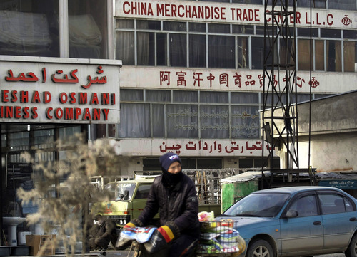 In this Tuesday, Jan. 22, 2013 photo, an Afghan man rides his bike past a China Merchandise Trade Center in Kabul, Afghanistan. China, long a bystander to the bloody conflict in neighboring Afghanistan, is accelerating its involvement as U.S.-led forces prepare to withdraw, attracted by its vast, untapped mineral resources and concerned that post-2014 chaos could fuel its own Islamist insurgents. (AP Photo/Musadeq Sadeq)