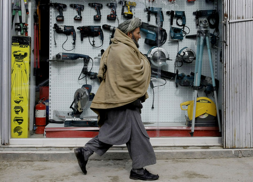 In this Tuesday, Jan. 22, 2013 photo, an Afghan man walks past a shop selling tools made in China, in Kabul, Afghanistan. China, long a bystander to the bloody conflict in neighboring Afghanistan, is accelerating its involvement as U.S.-led forces prepare to withdraw, attracted by its vast, untapped mineral resources and concerned that post-2014 chaos could fuel its own Islamist insurgents. (AP Photo/Musadeq Sadeq)