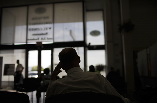 FILE- In this Thursday, April 23, 2009, file photo, Jerald Vance, 50, is silhouetted as he waits to talk to a job counselor at a Nevada Jobconnect Career Center in Las Vegas. An Associated Press investigation released in January 2013 found that millions of mid-skill, mid-pay jobs have disappeared over the past five years and have been replaced with technology. That experience has left a growing number of technologists and economists wondering if middle-class jobs will return when the global economy recovers, or are they lost forever because of the advance of technology. (AP Photo/Jae C. Hong, File)