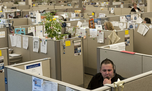 FILE - In this Dec. 19, 2012 photo, James Finch, front, service advisor for U.S.Bank Service Center, takes a call at the facility in Coeur d'Alene, Idaho. An Associated Press investigation released in January 2013 found that millions of mid-skill, mid-pay jobs have disappeared over the past five years and have been replaced with technology. That experience has left a growing number of technologists and economists wondering if middle-class jobs will return when the global economy recovers, or are they lost forever because of the advance of technology. (AP Photo/The Spokesman-Review, Kathy Plonka)  COEUR D'ALENE PRESS OUT