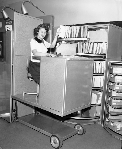 FILE - In this March, 6, 1953, file photo, Jane Martin remains seated and files paperwork using a hydraulic lift in Chicago, Ill.  An Associated Press investigation released in January 2013 found that millions of mid-skill, mid-pay jobs have disappeared over the past five years and have been replaced with technology. Peter Lindert, an economist at the University of California-Davis, does not believe workers are doomed to unemployment. With the right skills and education, Lindert says, workers can learn to work with the machines and become productive enough to fend off the automation threat.  (AP Photo/Edward Kitch, File)