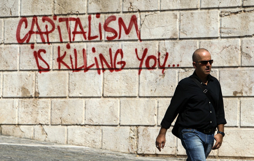 "FILE - In this Tuesday, Sept. 25, 2012, file photo, a pedestrian walks in front of graffiti in Athens. In a speech in 2012, former U.S. Treasury Secretary Lawrence Summers declared that the biggest economic issue of the future would not be the federal debt or competition from China but ""the dramatic transformations that technology is bringing about.'' (AP Photo/Thanassis Stavrakis, File)"