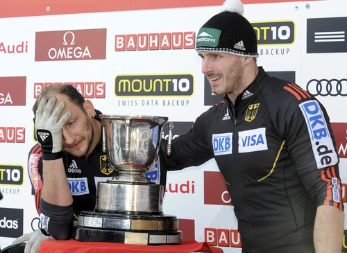 Third placed Thomas Florschuetz, left, is comforted by his brakeman Andreas Bredau, right, both from Germany, after the 2-man Bobsled World Championship competition in St. Moritz, Switzerland, Sunday Jan.  27, 2013. (AP Photo/Keystone/Karl Mathis)
