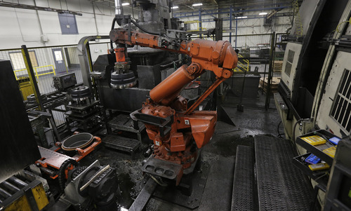 In this Friday, Jan. 11, 2013, photo, a robot lifts and stacks brake drums at Webb Wheel Products in Cullman, Ala. Webb Wheel hasn't added a factory worker in three years, though it's making 300,000 more drums annually, a 25 percent increase, because of robots. (AP Photo/Dave Martin)