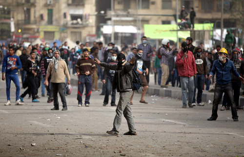 Egyptian protesters clash with riot police, not seen, near Tahrir Square, Cairo, Egypt, Sunday, Jan. 27, 2013. Clashes continued for the fourth successive day between protesters and police near Cairo's central Tahrir square, birthplace of the 2011 uprising. Police used tear gas, while the protesters pelted them with rocks. (AP Photo/Khalil Hamra)