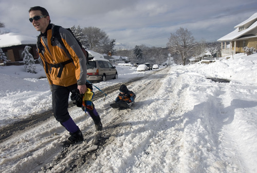 Kim Raff  |  The Salt Lake Tribune Chris Pasko pulls his son Jasper Pasko on a sled up the middle of Kensington Avenue the morning after a winter storm in Salt Lake City on Monday, Jan. 28, 2013.