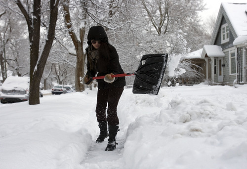 Kim Raff  |  The Salt Lake Tribune May Lawley shovels the sidewalk on 800 East the morning after a winter storm in Salt Lake City on Monday, January 28, 2013.