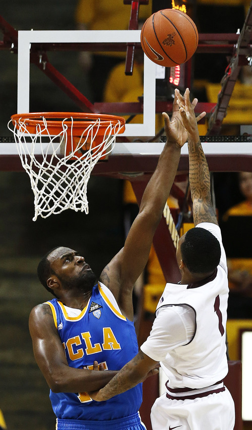 Arizona State's Jahii Carson (1) shoots over UCLA's Shabazz Muhammad during the first half of an NCAA college basketball game, Saturday, Jan. 26, 2013, in Tempe, Ariz. (AP Photo/Ross D. Franklin)
