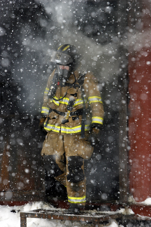 Francisco Kjolseth  |  The Salt Lake Tribune Firefighter John Hill exits a burning training building as the Salt Lake City Fire Department trains on a live fire drill to test thermal imaging cameras. The cameras allow firefighters to see the different gradations of heat in a structure which can assist in finding victims or hot spots as they navigate smoke-filled environments.