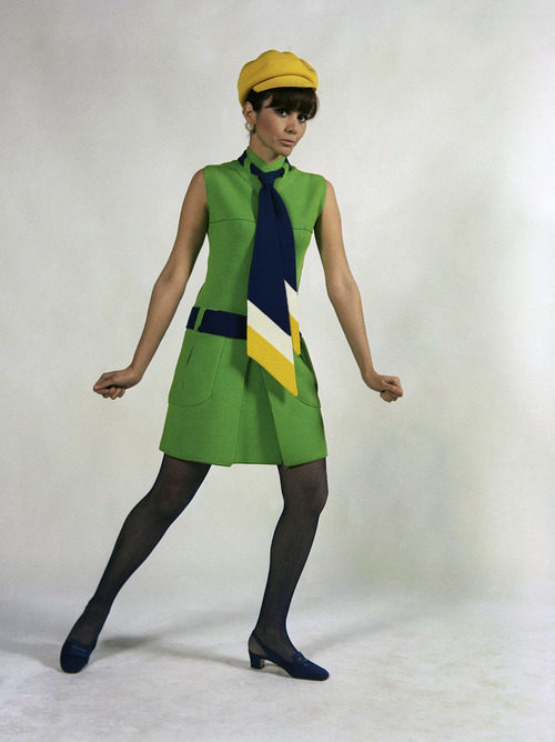 An original short tunic of sun green jersey, worn with a long, college-type necktie, blue, white and yellow, with a yellow cap, blue belt, and black stockings. A creation of Albertina house of Rome, presented at Florence, Jan. 18, 1967. (AP Photo)