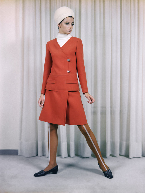 A tailored dress of rust-red wool, worn with a white jersey bodice, a creation by the Irene Galitzine fashion house of Rome, July 23, 1968, presented at its show of its fall and winter collection on July 17. The small hat is by the Canessa house of Rome. (AP Photo/Mario Torrisi)