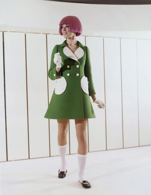 Green woolen coat with round pockets and white reverse was shown by the Andre Courreges fashion house during the Paris Spring and Summer showings in 1969. Buttons are white and the model wears a bright colored wig, White cotton socks and black leather flat holed shoes. (AP Photo)