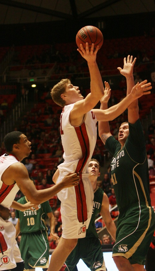 Kim Raff  |  The Salt Lake Tribune University of Utah player (left) Dallin Bachynski shots the ball over  Sacramento State player Konner Veteto during a men's basketball game at the Huntsman Center in Salt Lake City on November 16, 2012. They went on to lose the game 71-74.