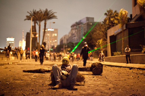 "In this Monday, Jan. 28, 2013 photo, an Egyptian protester takes a break while others use green laser pointers during clashes between protesters and Egyptian security forces in Downtown Cairo, Egypt. On Tuesday, Jan. 29, 2013, Egypt's army chief warned of ""the collapse of the state"" if the political crisis continues. (AP Photo/Virginie Nguyen Hoang)"