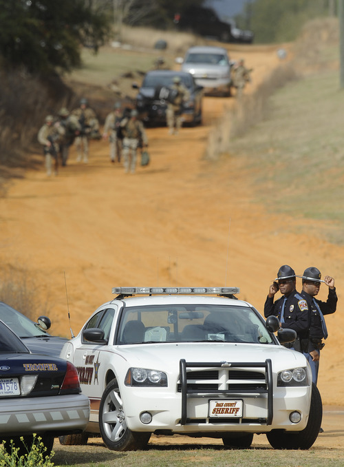 Police SWAT teams and hostage negotiators are gathered at standoff and hostage scene in Dale County near Ozark, Ala. on Wednesday Jan. 30, 2013. Authorities were locked in a standoff Wednesday with a gunman authorities say on Tuesday intercepted a school bus, killed the driver, snatched a 6-year-old boy and retreated into a bunker at his home in Alabama. (AP Photo/Montgomery Advertiser, Mickey Welsh) (AP Photo/The Montgomery Advertiser, )  NO SALES