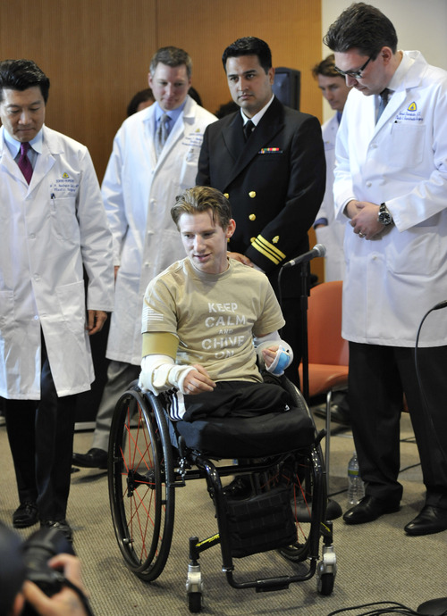 Retired Infantryman Brendan M. Marrocco wheels himself into a news conference followed by surgeons, from left, W.P. Andrew Lee, M.D., Jamie Shores M.D., Patrick L. Basile M.D. and Gerald Brandacher M.D. Tuesday, Jan. 29. 2013 at Johns Hopkins hospital in Baltimore.  Marrocco received a transplant of two arms from a deceased donor after losing all four limbs in a 2009 roadside bomb attack in Iraq. (AP Photo/Gail Burton)
