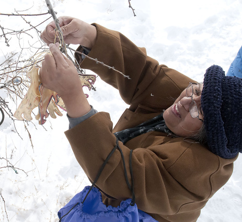 Patty Timbimboo-Madsen ties an offering to her ancestors onto a tree during the 150th anniversary memorial ceremony of the Bear River Massacre, Tuesday, Jan. 29, 2013 near Preston, Idaho. (Eli Lucero/Herald Journal)