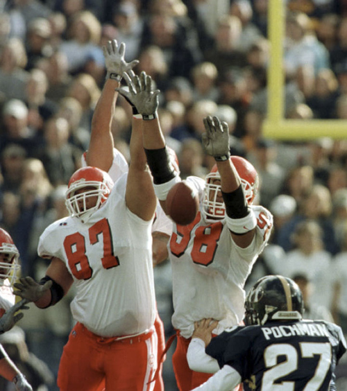 Utah's Richard Seals (87) and Ma'ake Kemoeatu (98) block a field goal attempt by Owen Pochman during their game in 1999. Utah went on to win the game 20-17. Courtesy of University of Utah Athletics
